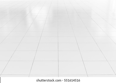 White tile floor background in perspective view. Clean surface and symmetry with grid line texture or pattern. For decoration in bathroom, kitchen and laundry room.