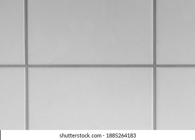 White tiles and gray joints on the wall