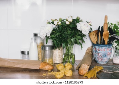 White tiles wall modern kitchen with chopping board,flowers,knifes,pasta,bread. White tiles wall modern kitchen with white top background and ingredients