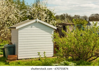 White tiny house or shed at a plot of an allotment. Affordable property.