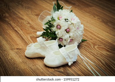 White tiny shoes and white bouquet on a wooden floor