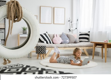 White tire on line above black and white patterned carpet in cute girly scandi room
