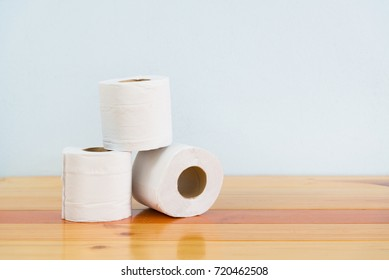 White tissues paper or toilet paper on brown wooden table over white wall with copy space.