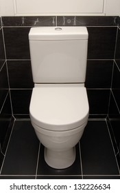 The white toilet bowl is in a black interior.