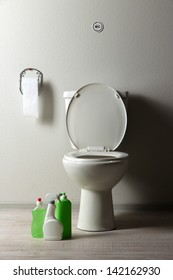 White toilet bowl and  cleaning supplies in a bathroom