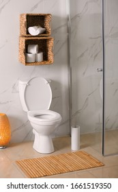 White toilet bowl near marble wall in bathroom