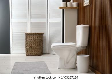 White toilet bowl near wooden wall in modern bathroom interior