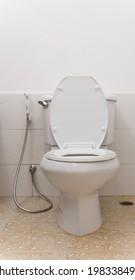 White toilet bowl and Toilet Sprayer in bathroom