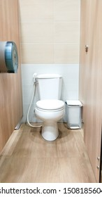 White toilet, garbage bin, placed beside the paper box, holds blue, brown wall floor
