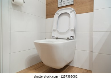 White toilet on the wall with opened lid.
