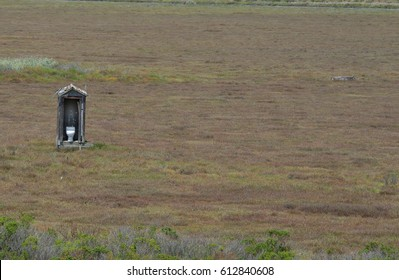 White toilet in outhouse out in open filed