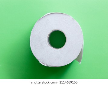 White toilet paper on green background. Above view