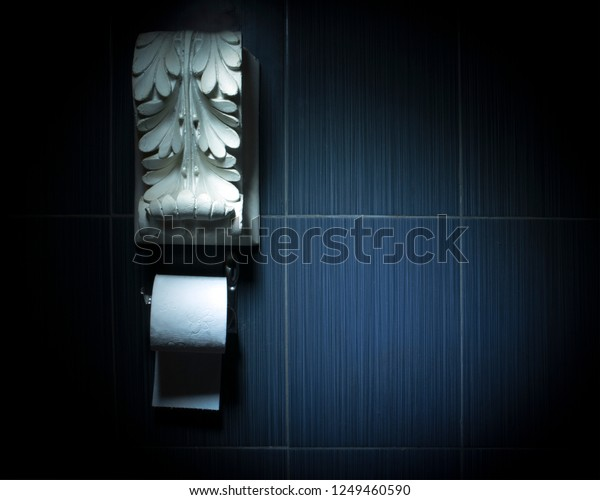 White toilet paper roll on chrome fixture with white antique plaster decoration above. Conceptual toilet design