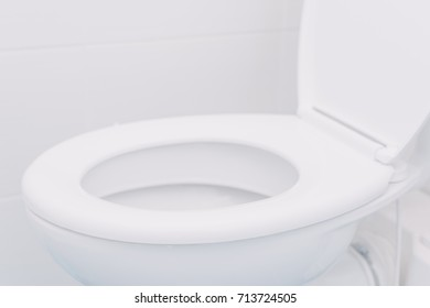 White toilet seat in bathroom, selective focus with copy space