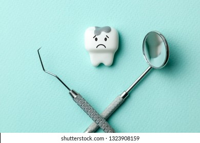 White tooth with caries is sad on green mint background  and dentist tools mirror, hook