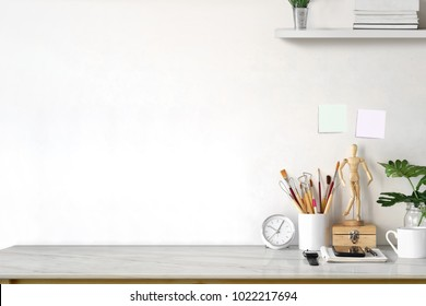 White top desk with brush, coffee cup and artist accessories with copy space.  workspace and designer accessories.