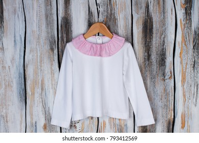 White top with pink collar rustic wooden background. Soft fabric and cute girlish details. Girls clothing collection.
