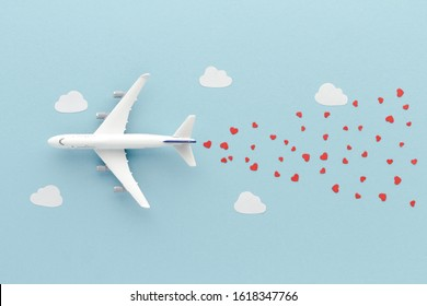 White top view Airplane . Hearts clouds blue airplane cloud sky background with copy space for your text. Flat lay.