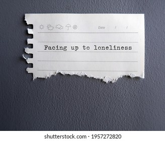 White torn note stick on gray wall with text typed FACING UP TOO LONELINESS - concept of accept and embrace loneliness, facing up to living alone , become more at peace and content