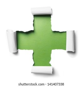 white torn paper with plus shape over green background