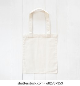 White tote bag mock up, fabric canvas cloth shopping sack template on wood table background