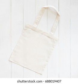 White tote bag mock up, fabric canvas cloth eco shopping sack template on wood table background