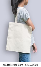 White tote bag mockup cotton canvas fabric texture on girl shoulder (clipping path) in white cream color isolated on purple background