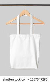 White tote bag mockup hanging on a clothes hanger.