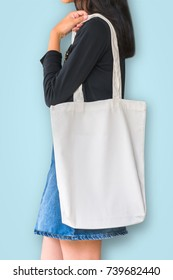 White tote bag mockup template cotton canvas fabric texture on girl shoulde on blue background
