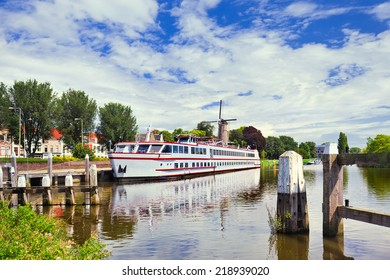 White tour-boat moored in a tranquil canal with a windmill on the background, Gouda, The Netherlands