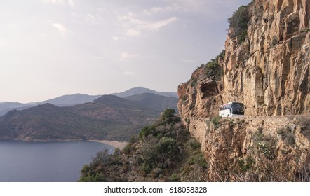 A white tourist bus on a Mediterranean mountain road on a cliff of a sunny bay