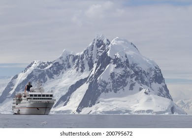 White tourist ship a summer day on a background of mountains of the Antarctic Peninsula