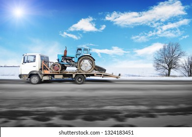 White tow truck driving fast with old blue tractor on the winter countryside road against blue sky with sun