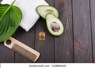 White towel, avocado, little glass bottle and wooden comb for hair lie on a wooden table