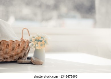 White towel in basket on white table with copy space on blurred living room background. For product display montag