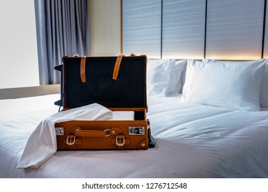 White Towel in Brown Suitcase on the Bed.
