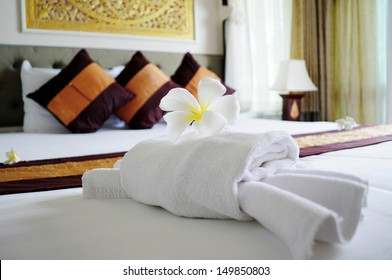 White towel in crab shape and a frangipani flower on white bed in relaxation bedroom of luxury boutique hotel