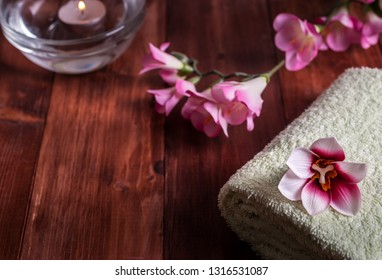 White towel with flowers and a burning candle on a wooden background. Selective focus