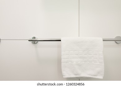 White towel hanging on the clothes rack in the bathroom in the hotel