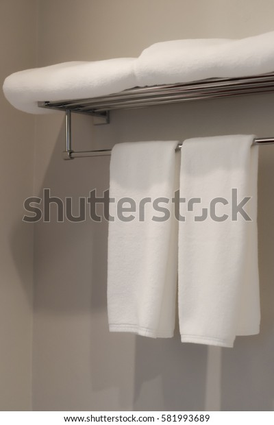 white towel laid on racks in the bathroom prepared to use. with soft focus