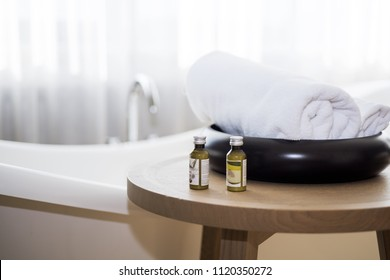 White towel and massage bath oil on table in bathroom. Abstract SPA photo.
