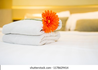 White towel on bed with flower  decoration in bedroom interior.Hotel service