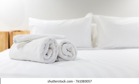 White towel on bed in guest room for hotel customer.
