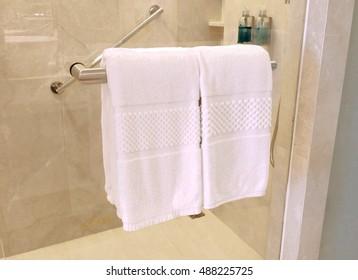 white towel on a hanger prepared to use in bathroom.