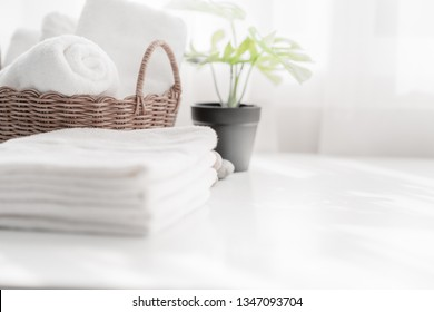 White towel on white table with copy space on blurred living room background. For product display montage