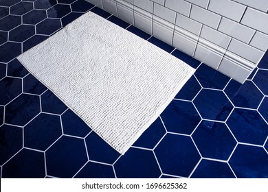 White towel on the tile blue floor. Top view on hexagon ceramic bathroom