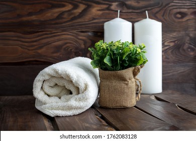 A white towel rolled up on a wooden background, next to flowers and candles. Concept of relaxation, recreation, Spa and saunas.