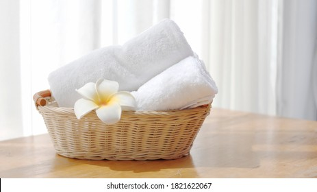 White towels in a basket placed on a table with natural light, spa ideas and toiletries.