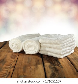 white towels brown table and soap with bokeh background