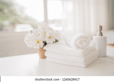 White towels, ceramic soap, shampoo bottle with copy space on blurred living room background. For product display montage